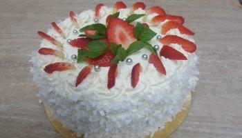 Tort śmietankowy ozdobiony truskawkami i miętą